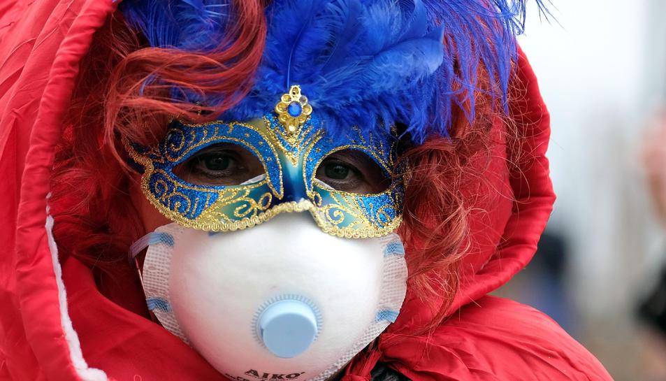 Una persona amb la màscara de Carnaval i una mascareta de paper pel coronavirus a Venècia