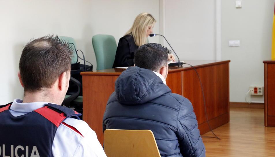 L'acusat d'intentar llançar la seva exparella per la finestra a Lleida, al jutjat penal 3 de Lleida, custodiat per un Mosso, i amb la seva advocada al fons.