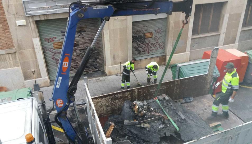 Operaris de neteja retirant els contenidors cremats al carrer de la Selva del Camp.