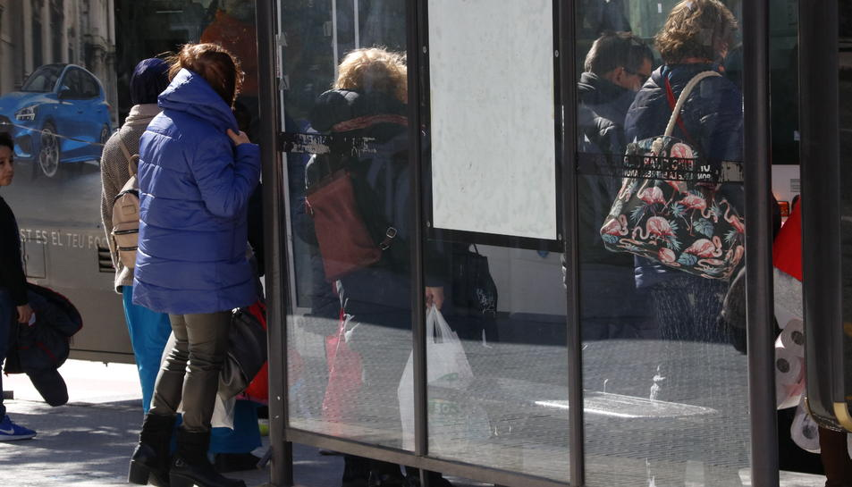 Gent protegint-se del vent, en una parada d'autobús a Valls.