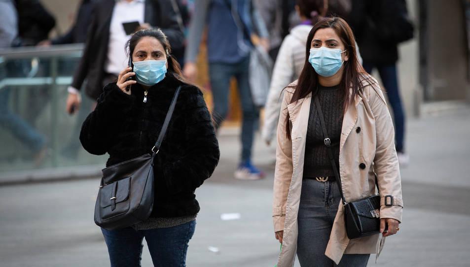 Dues dones amb mascarilles caminant per Barcelona