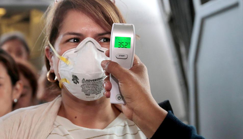 Un metge prenent la temperatura a una dona per comprobvar si té