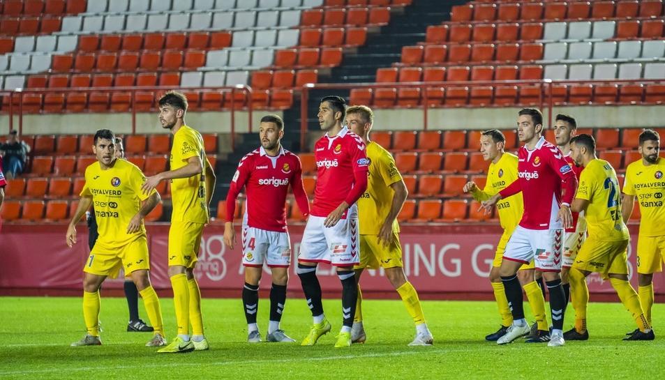 David Goldar, Gerard Oliva i Juan Rodríguez envoltats de jugadors de l'Olot durant el duel de Copa del Rei d'aquesta temporada.