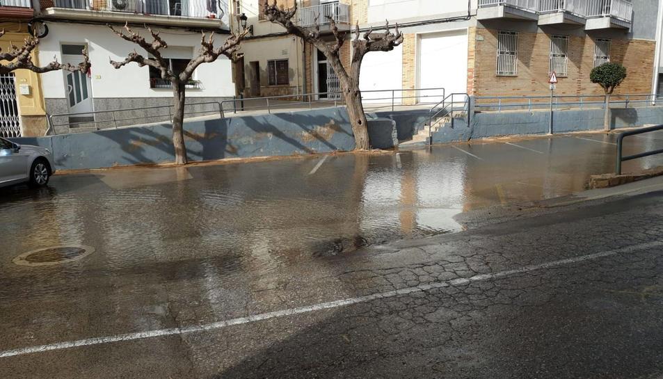 Pla general d'un carrer de l'Ampolla inundat per la baixada dels barrancs arran la reparació de la canonada.