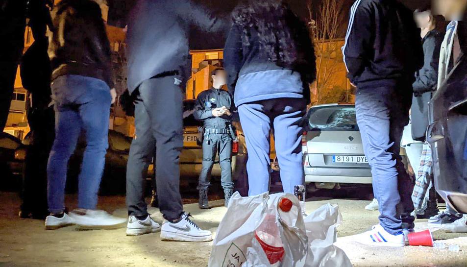 Agents de la Guàrdia Urbana de Reus, de nit, denunciant un grup de joves per consumir alcohol a la via pública.