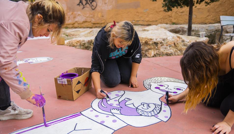 Artigal, a l'esquerra, retocant el dibuix de la plaça de la Dona Treballadora amb els últims detalls.