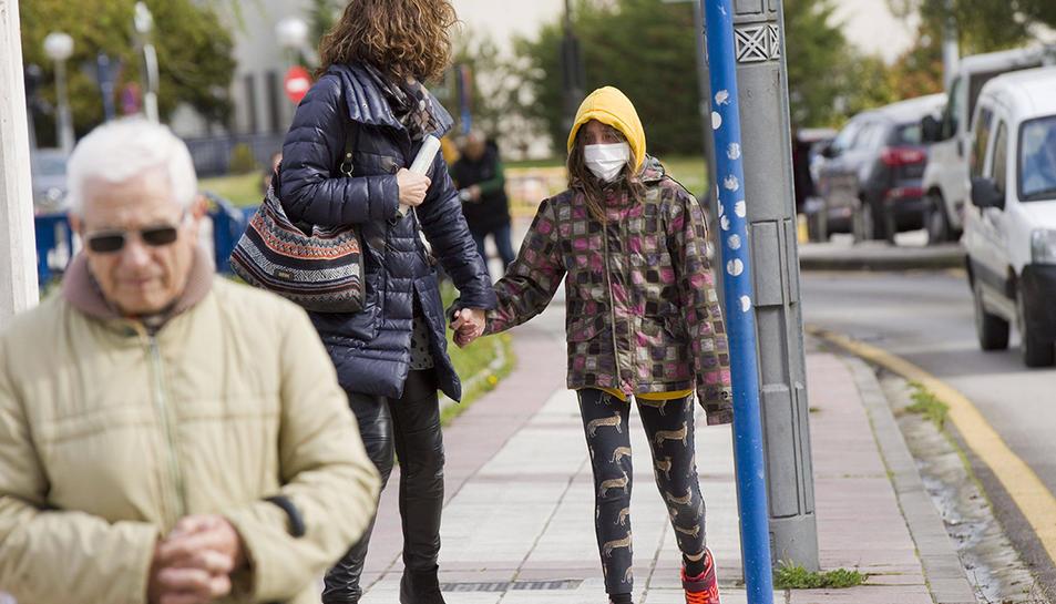 Una noia amb  màscara caminant amb la seva mare pel carrer.