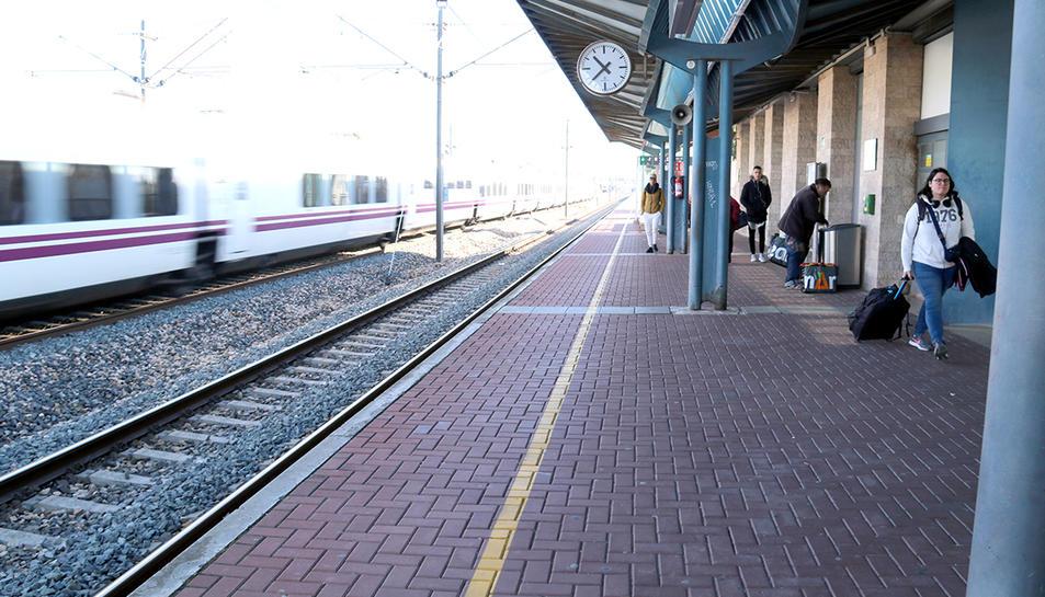 L'estació de l'Aldea-Tortosa-Amposta, amb viatgers a l'andana mentre un tren ràpid passa de llarg sense fer parada.