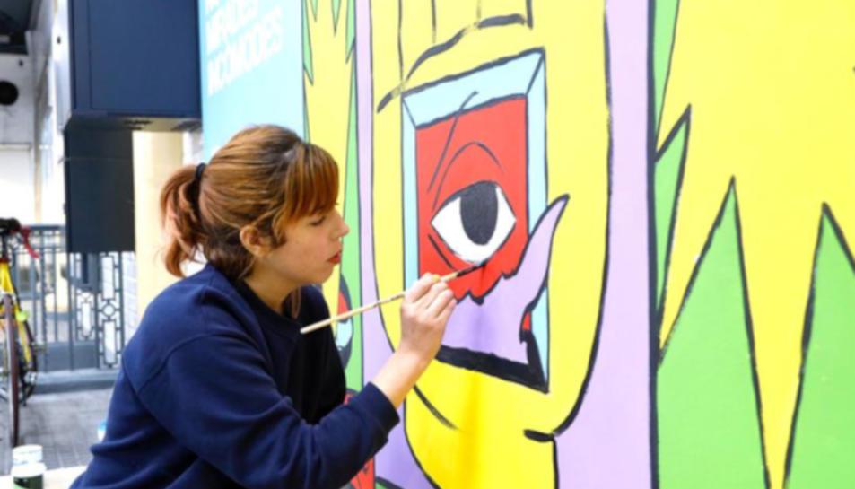 La il·lustradora Cristina Daura mentre pinta un mural en el marc de la campanya 'Tolerància Zero' d'FGC
