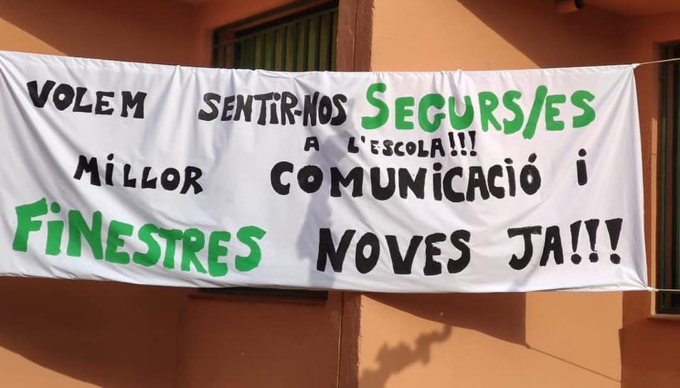 Imatge de la pancarta penjada al centre educatiu que reclama finestres noves i més seguretat.