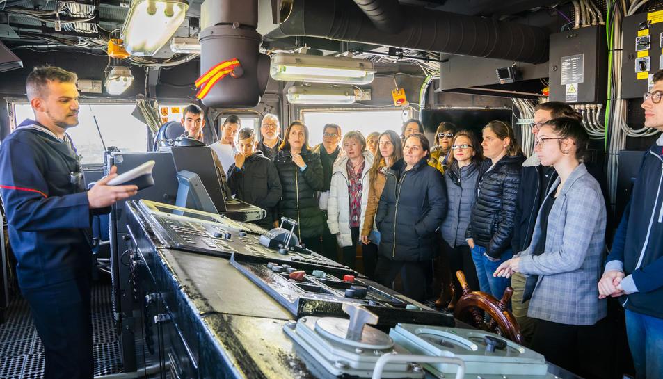 Un membre de la tripulació mostrant l'interior del Vigía als visitants.