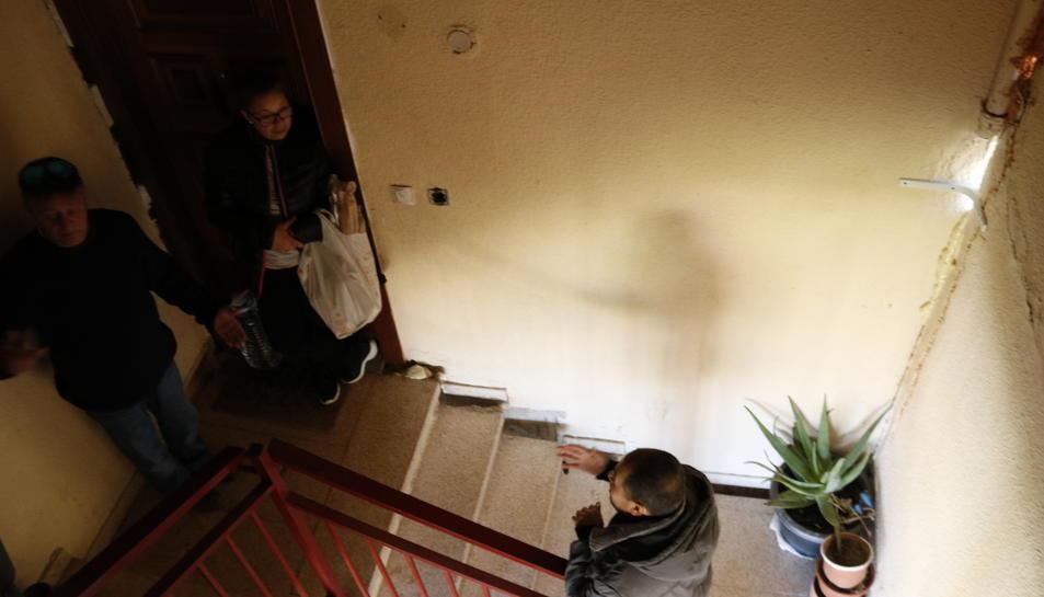 Veïns conversant, indignats, per les greus esquerdes que pateixen a l'escala d'un bloc de pisos al barri Centcelles de Constantí.