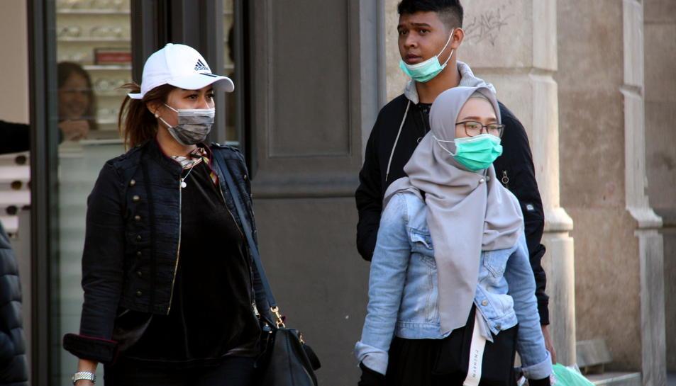 Gent passejant per Barcelona amb mascaretes.