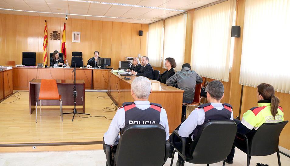 La sala de vistes de l'Audiència de Tarragona, amb tres agents dels Mossos en primer terme, amb l'acusat assegut, d'esquenes, a la dreta.