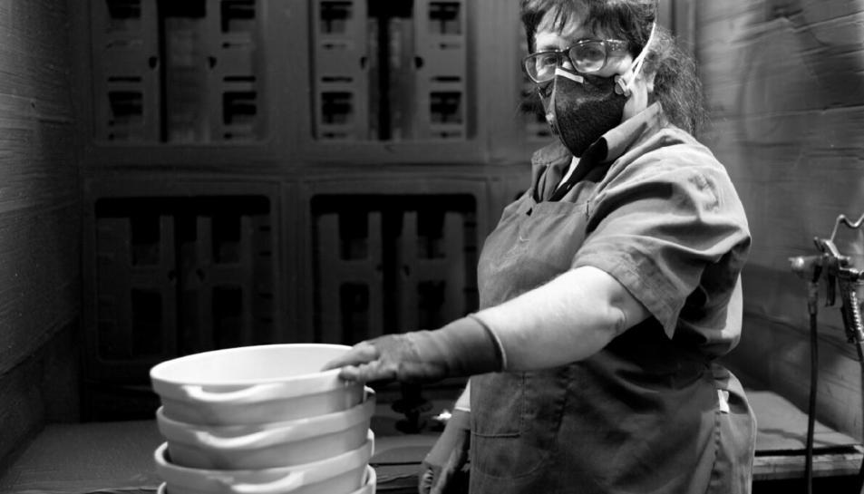 Una de les treballadores de la fàbrica de Valira, a Reus, amb guants i mascareta per prevenció.