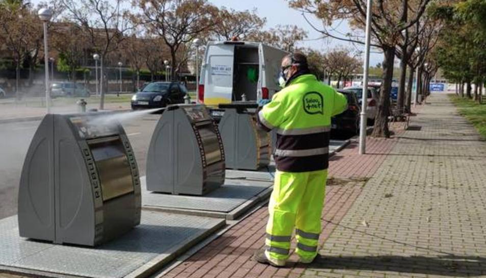 Un operari neteja un contenidor a Salou