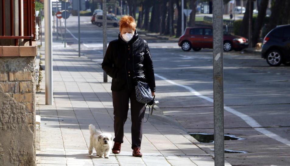 Una senyora amb màscara passejant el seu gos per l'avinguda del Canal de Mollerussa on s'hauria d'estar celebrant la Fira de Sant Josep, suspesa pel coronavirus