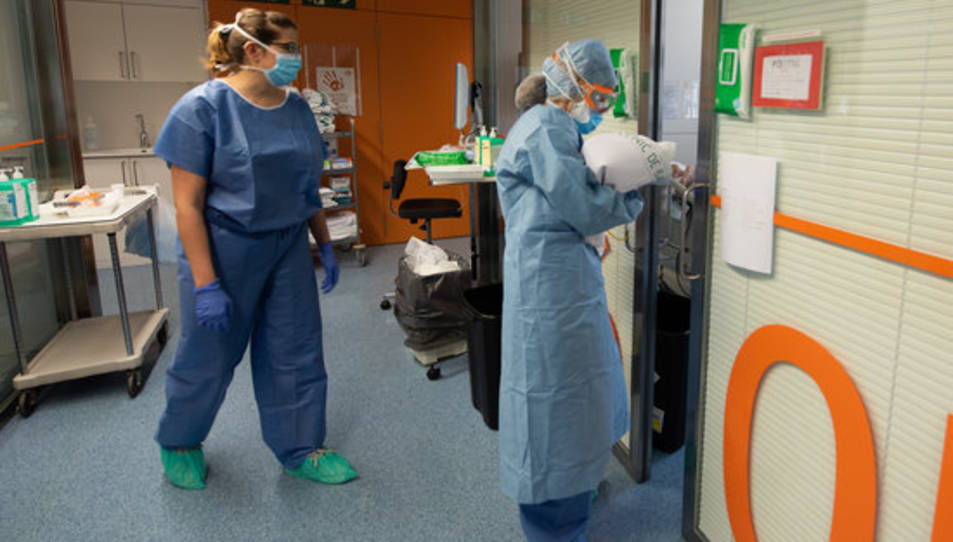 Una professional sanitària entra en una habitació ocupada per un positiu per coronavirus a l'Hospital Clínic.