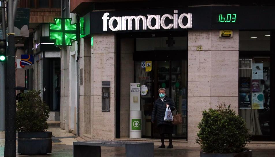 Imatge d'una dona sortint d'una farmàcia a Tortosa.