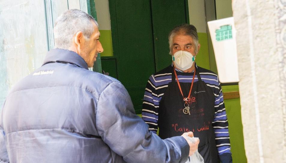 Un usuari ahir, agafant el menjar oferit per Càritas, en el programa Cafè i Caliu.