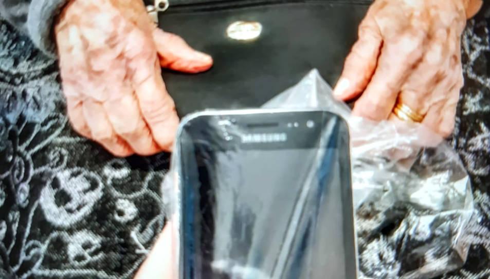 Primer pla d'un telèfon mòbil protegit amb un plàstic a punt perquè una àvia de la residència Natzaret de Móra d'Ebre rebut una videotrucada dels seus familiars.