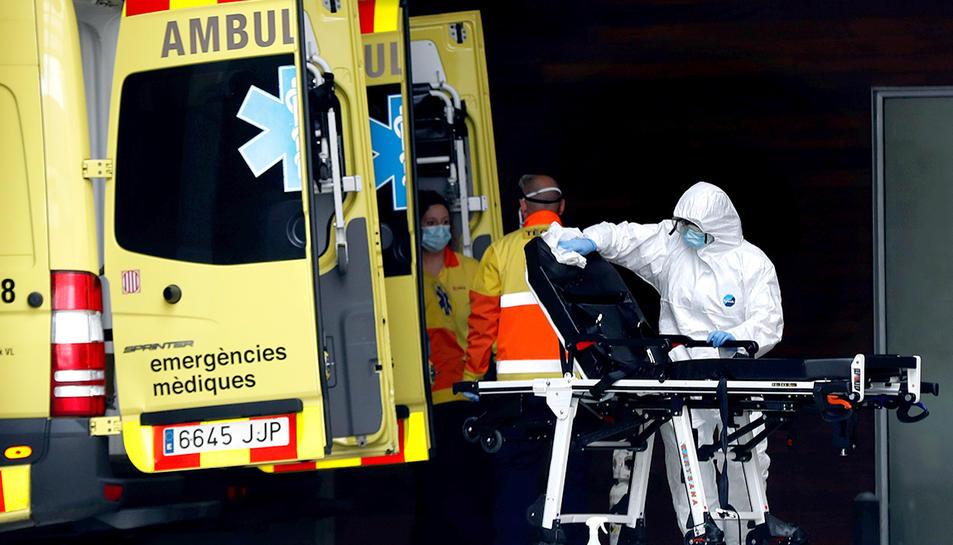 Un tècnic sanitari desinfectant una llitera d'una ambulància.