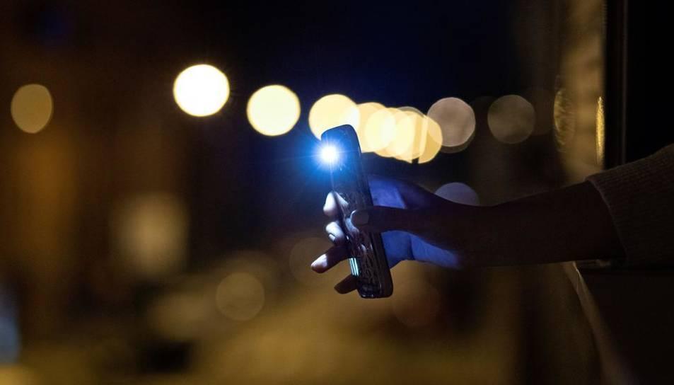 Un mòbil amb la llum de la llanterna encesa.
