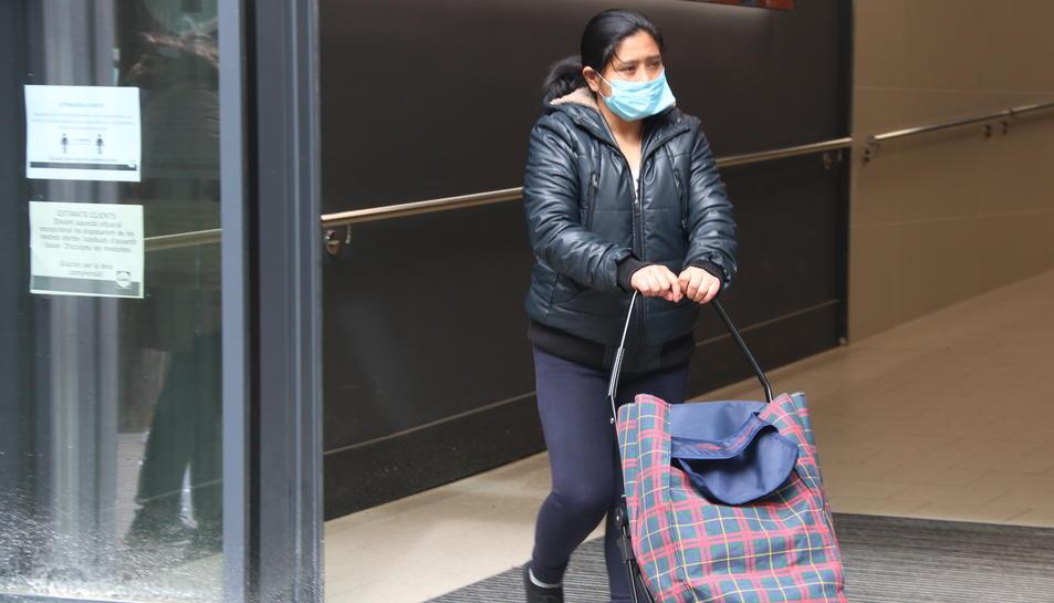 Pla tancat d'una client que porta mascareta sortint d'un supermercat a Barcelona.