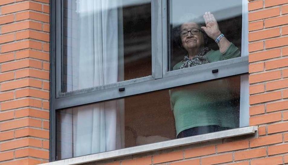 Una dona saluda des d'una residència