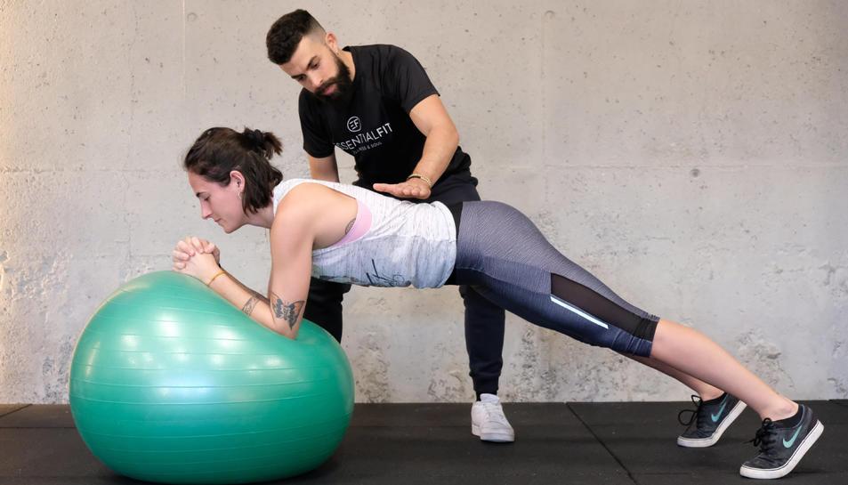 El director del gimnàs Essential Fit ajudant a una alumna a fer bé l'exercici en una imatge d'arxiu