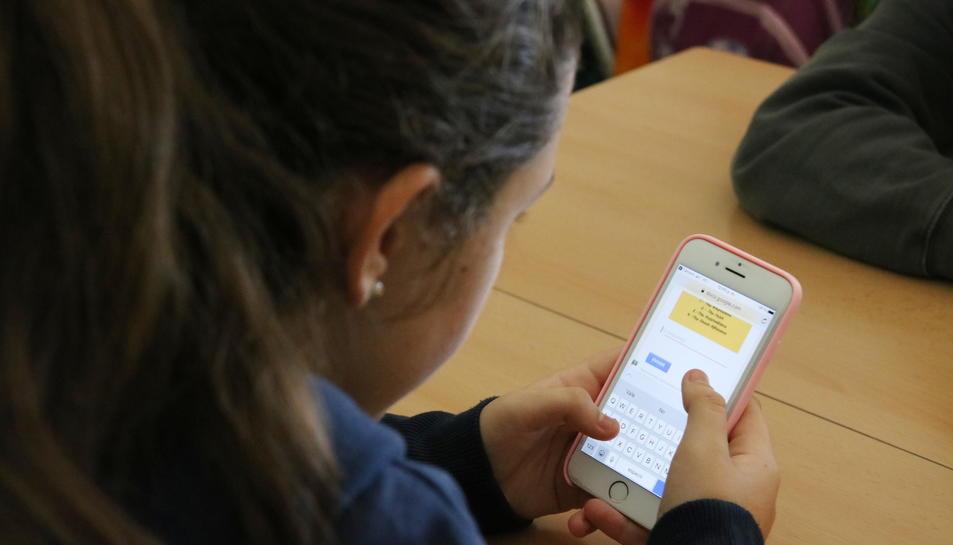 Pla escorç d'una jove fent servir el mòbil a classe.