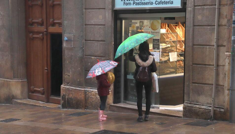 Una dona i una nena, a punt d'entrar en una pastisseria del carrer Comte de Rius de Tarragona.