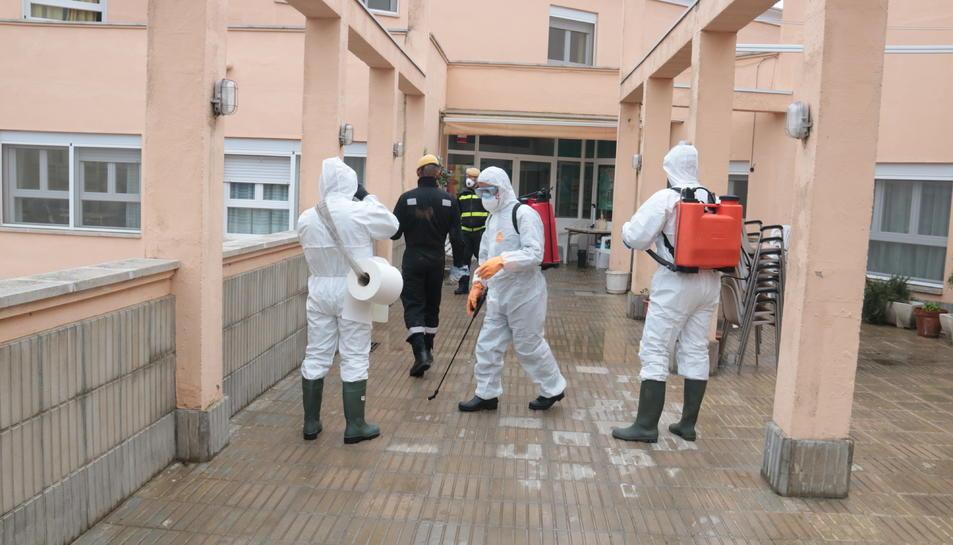 Efectius de l'excèrcit a l'entrada de la residència d'Àger, equipats per definfectar-la.