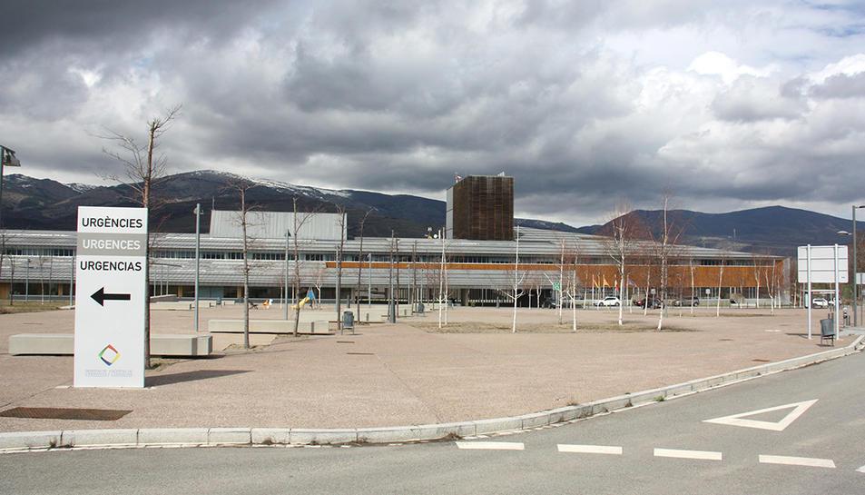 Exterior de l'edifici de l'Hospital de Cerdanya, on es veu en primer terme un cartell que indica on està la zona d'Urgències.