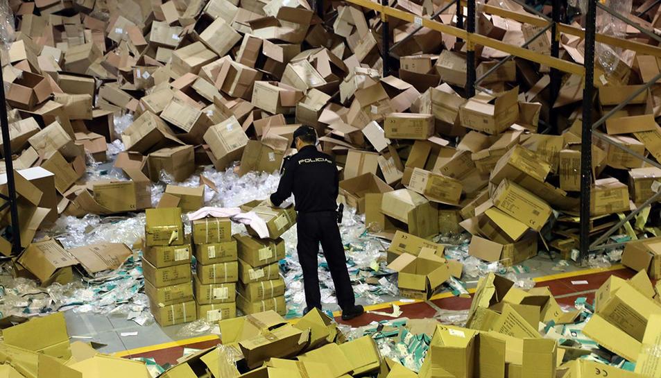 Un agent revisant caixes al magatzem de l'empesa que va ser robada.