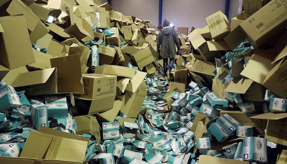 Un fotògraf caminant per sobre les caixes buides on havia el material robat.