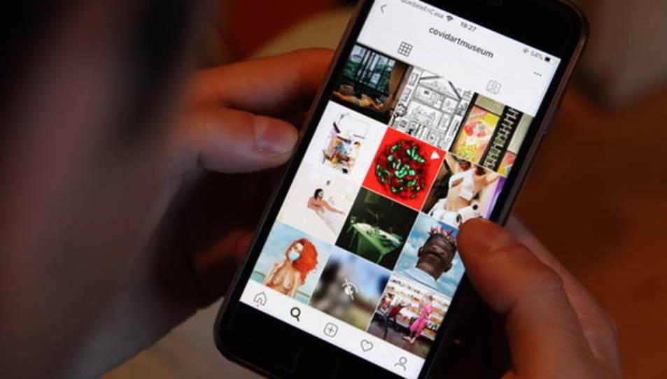 Una persona mira publicacions a Instagram de The Covid Art Museu.