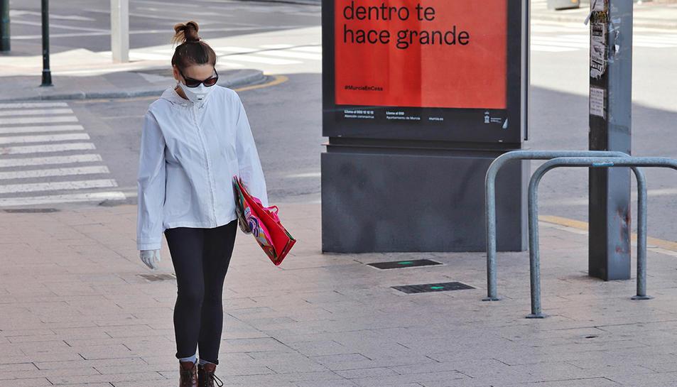 Una dona amb mascareta caminant perl carrer.
