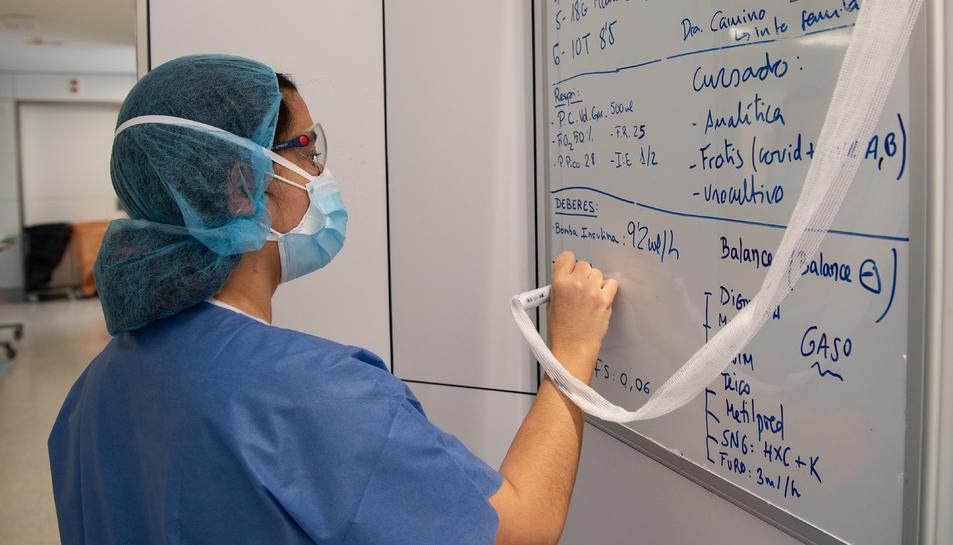 Una professional sanitària pren notes en una pissarra dels tractaments i proves als pacients amb covid-19 en un dels blocs quirúrgics de l'Hospital Clínic de Barcelona habilitat com a UCI en la pandèmia de coronavirus.