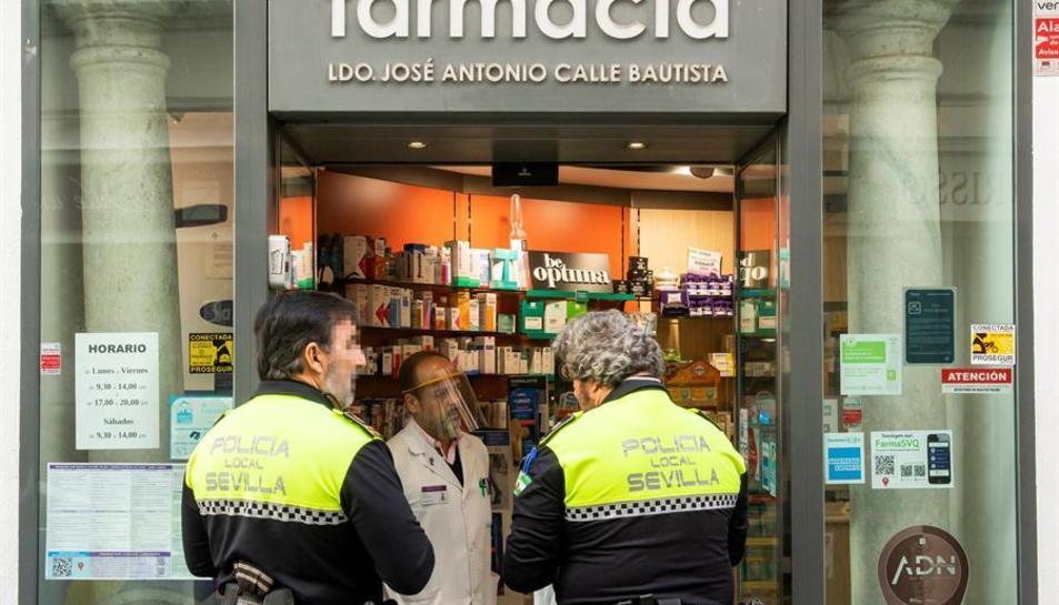 Dos agents de la policia local de Sevilla a l'entrada d'una farmàcia.