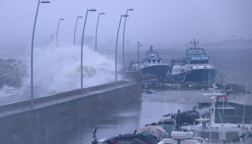 Una gran onada batent contra el moll del port de l'Ampolla amb les barques de pesca amarrades a l'interior.
