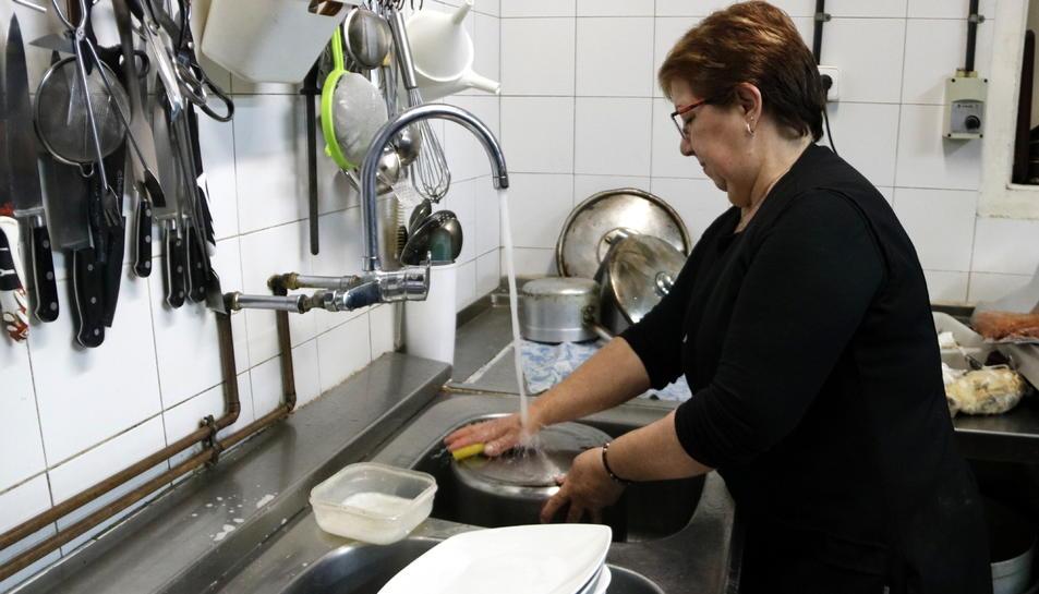 Pla general d'una dona de Castellolí mentre frega els plats amb l'aigua de l'aixeta.