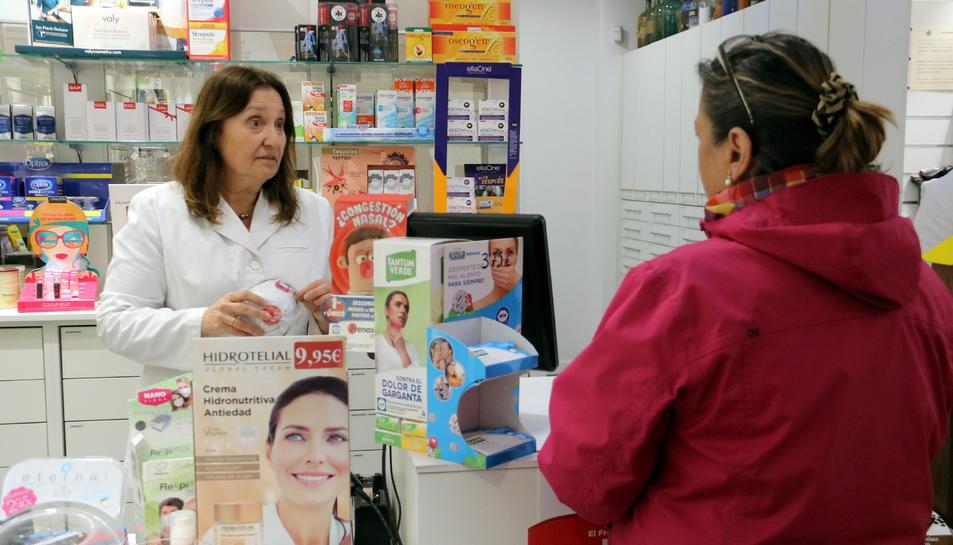 La responsable de la farmàcia Noguera de Girona ensenyant les mascaretes que els queden als compradors.