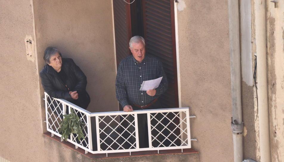Pla mitjà d'un participant de la Setmana Santa de la Selva del Camp interpretant els temes de la processó de l'Agonia de Divendres Sant des del balcó de casa seva.