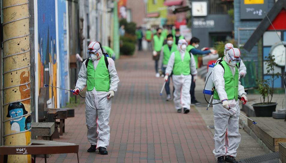 Treballadors desinfecten un carrer a Corea del Sur