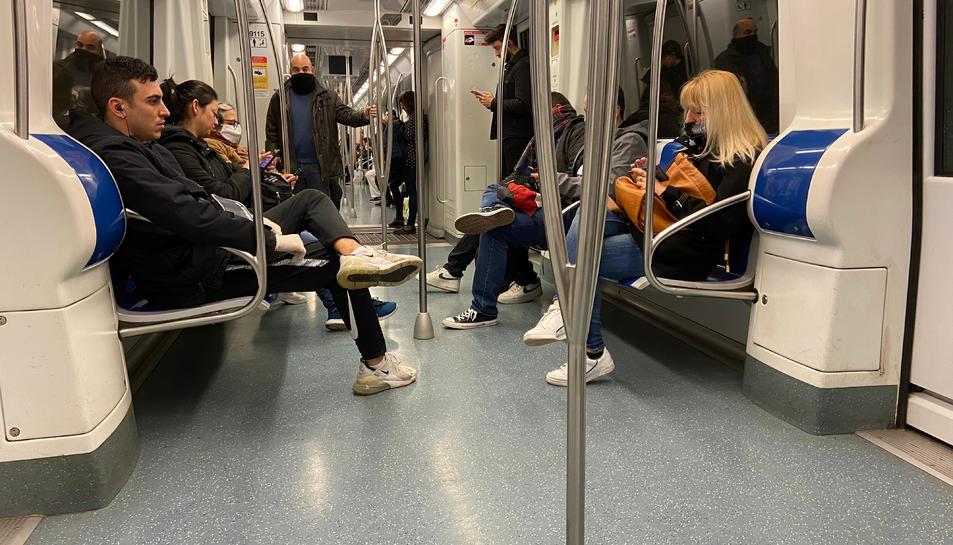 Interior d'un vagó de metro de la línia groga durant l'hora punta del segon dia feina d'estat d'alarma, el 17 de març