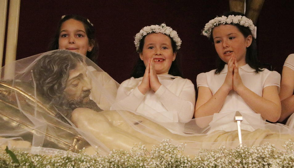 Pla mig de tres nenes vestides de comunió durant la Coronació del Senyor a Reus, davant del Crist Rei.