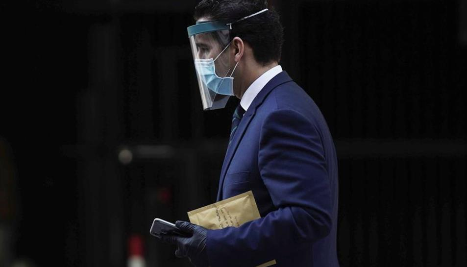 Un home camina amb una mascareta de protecció.