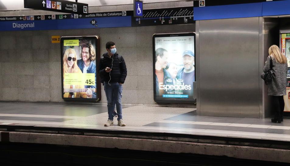 Un home amb mascareta esperant el metro a l'andana de l'estació de Diagonal de Barcelona.