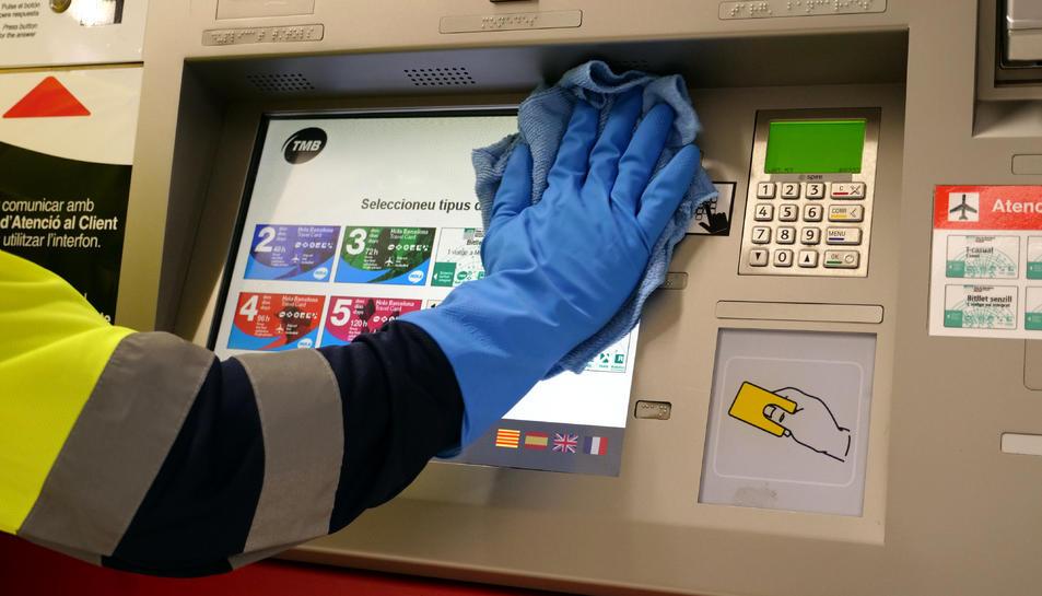 Un treballador de TMB neteja una màquina de venda de bitllets.